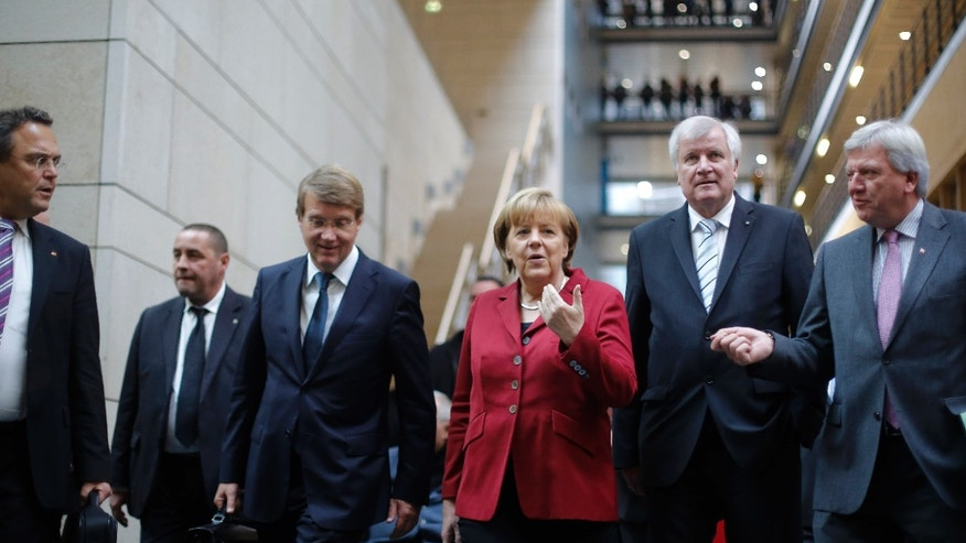 From right, Hesse state governor Volker Bouffier, Bavarian governor Horst Seehofer, German Chancellor and chairwoman of the Christian Democrats, CDU, Angela Merkel, Chief of Staff at the chancellery Ronald Pofalla and Interior Minister Hans-Peter Friedrich, left, walk to exploratory talks about an coalition with the Social Democratic Party, SPD, in Berlin, Thursday, Oct. 17, 2013. Following the national elections on Sept. 22, 2013, Merkel is still in negotiations for a coalition partner for her third term. (AP Photo/Markus Schreiber)