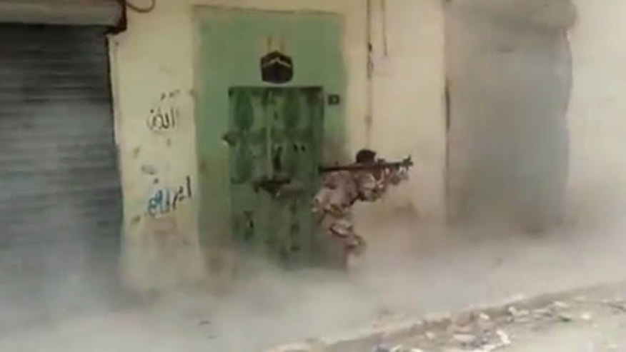FILE - This Wednesday, May 29, 2013 file image made from video posted by Shaam News Network, which is consistent with other AP reporting, shows a Free Syrian Army fighter firing a rocket propelled grenade in Aleppo, Syria, targeting a Syrian regime stronghold. (AP Photo)
