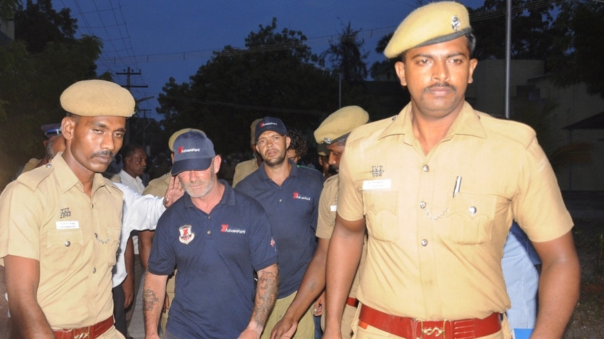 Oct. 18, 2013 - Indian policemen escort crew members of the U.S.-owned ship MV Seaman Guard Ohio outside a court in Tuticorin, in the southern Indian state of Tamil Nadu.   Police in the southern Indian port city arrested the crew on charges of illegally transporting weapons and ammunition in Indian waters.