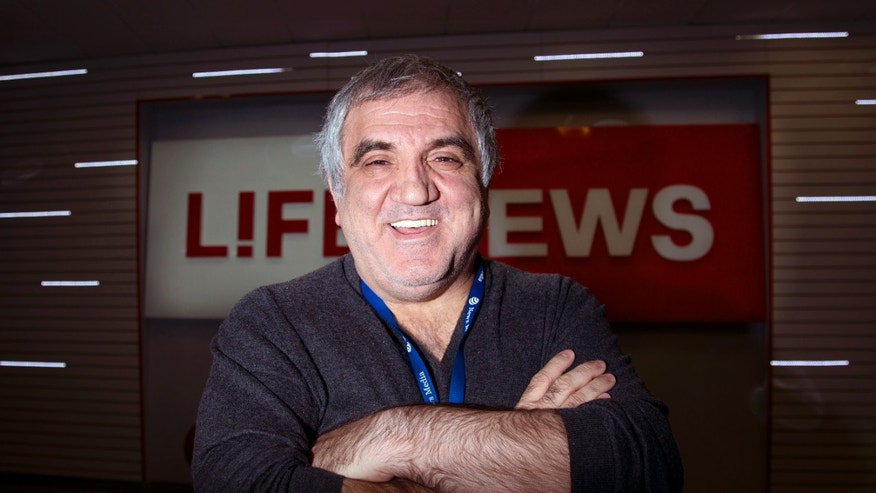Aram Gabrelyanov, Lifenews owner, smiles during the interview to The Associated Press in the company headquarters in Moscow on Monday, Oct. 14, 2013. Now the Gabrelyanovs' company, News Media Holding, earns $1.5 billion per year. In addition to Life, they own Izvestia, once the official newspaper of the Soviet government, as well as two tabloids and three websites. The younger son and inheritor of the empire, 24-year-old Ashot, runs Lifenews.ru as well as a new TV station. There is no substantive division between the holding's publications, which freely feed one another information and scoops, which are then retailored for each audience. The elder son, 26-year-old Artem, directs their comic book line, with a host of Russified superheroes that includes an Orthodox priest. (AP Photo/Ivan Sekretarev)