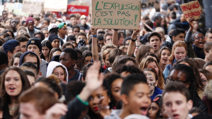 "High school students, one holding a poster ""Expulsion is not the Solution"", demonstrate against the police expulsions of immigrant families — including some of their classmates, Friday, Oct. 18, 2013 in Paris. Anger erupted this week over the treatment of a 15-year-old Kosovar girl who was detained in front of classmates on a field trip. The government says her eight-member family had been denied asylum and was no longer allowed to stay in France. (AP Photo/Christophe Ena)"