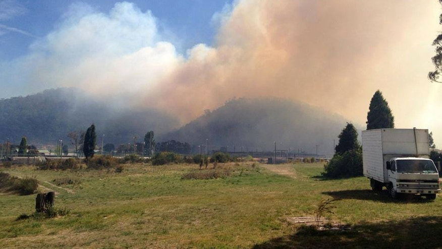 In this photo provided by the New South Wales Rural Fire Service, smoke rises from a fire near Lithgow, west of Sydney, Thursday, Oct. 17, 2013. Nearly a hundred wildfires are burning across Australia's New South Wales state, more than a dozen of which are out of control, as unseasonably hot temperatures and strong winds fanned flames across the parched landscape. (AP Photo/New South Wales Rural Fire Service)