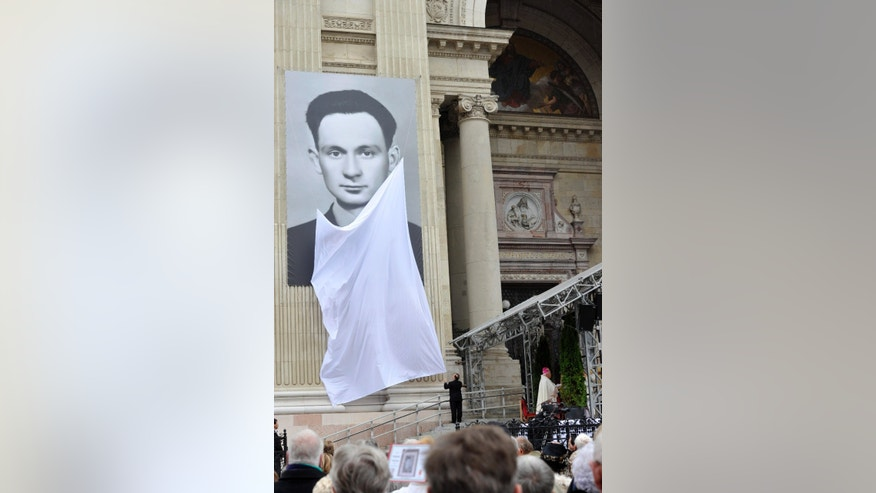 A portrait of Istvan Sandor, a Hungarian martyr monk of the Roman Catholic order of the Salesians of Don Bosco, is unveiled during a mass celebrated to beatify him in St. Stephen Square in front of St. Stephen Cathedral in Budapest, Hungary, Saturday, Oct. 19, 2013. Sandor was hanged June 8, 1953, by the communist regime after being convicted in a show trial of treason and conspiring against the state. The Catholic church recognizes him as a martyr. The indictment against Sandor and several others claimed that they wanted to bring down the communist regime and hoped for the victory of the United States in a new war. (AP Photo/MTI, Attila Kovacs)