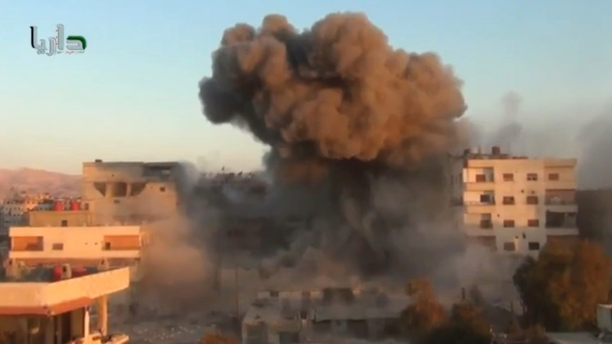 In this image taken from video obtained from the Shaam News Network, which has been authenticated based on its contents and other AP reporting, smoke billows amid buildings at a bomb explosion in Daraya, a countryside of Damscus, Syria, Tuesday, Oct. 15, 2013. Syrian warplanes bombed several rebel-held areas Tuesday and opposition fighters fired mortar rounds and homemade rockets at Damascus on the first day of a major Muslim holiday, activists said. (AP Photo/Shaam News Network via AP Video)