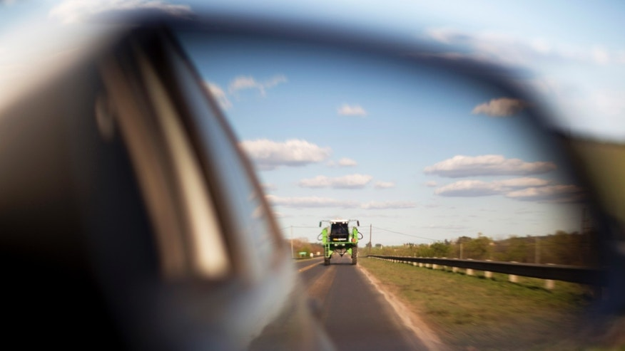 "In this Sept. 24, 2013, photo, a tractor used for spraying agrochemicals is reflected in a car's side view mirror on a road in Parana, in Entre Rios province, Argentina. Glyphosate represents two-thirds of all agrochemicals used in Argentina, but resistance to pesticides is forcing farmers to mix in other poisons such as 2,4,D, which the U.S. military used in ""Agent Orange"" to defoliate jungles during the Vietnam War. (AP Photo/Natcha Pisarenko)"