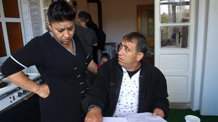 Resat and his wife Dzemila Dibrani look at a copy of the Italian birth certificate of daughter Leonarda Dibrani in a shelter house in the northern town of Mitrovica, Kosovo, Friday Oct. 18, 2013. The family were expelled from France as illegal immigrants last week and Leonarda Dibrani, taken by police from a school field trip last week, shocked many. Thousands of high school students protested in Paris angry at the expulsion of immigrant children and families like the Dibrani family. The demonstration came as the government was finalising a report on Friday into the treatment of a 15-year-old girl taken by police from a school field trip, then deported to Kosovo with her family as illegal immigrants. (AP Photo/Visar Kryeziu)