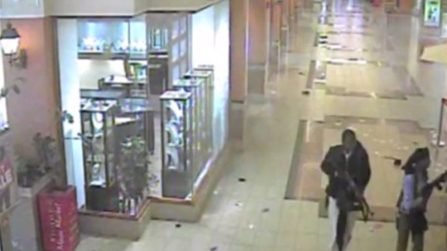 In this frame grab from surveillance video provided by Kenya Police via KTN, two gunmen wander through the Westgate Mall, Sept. 21, 2013, in Nairobi, Kenya. Several attackers from the Somali militant group al-Shabab stormed the mall on Sept. 21, killing at least 67 people during a four-day siege. (AP Photo/Kenya Police via KTN)