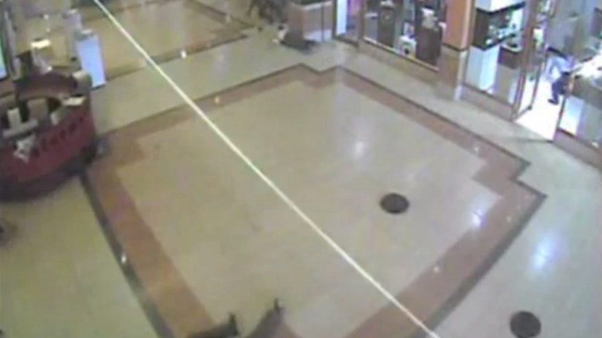 In this frame grab from surveillance video provided by Kenya Police via KTN, the streak of a bullet just fired from a gun, is seen as a guman fires his weapon inside the Westgate Mall, Sept. 21, 2013, in Nairobi, Kenya. Several attackers from the Somali militant group al-Shabab stormed the mall on Sept. 21, killing at least 67 people during a four-day siege. (AP Photo/Kenya Police via KTN)
