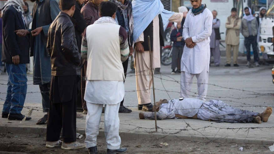 Afghans surround a dead man after a bomb exploded under a car, leaving the driver dead, in the center of Kabul, Afghanistan, Monday, Oct. 21, 2013. The Afghan Interior ministry confirmed that it was a magnetic bomb that destroyed the vehicle and killed the driver in the early morning rush hours. (AP Photo/Anja Niedringhaus)