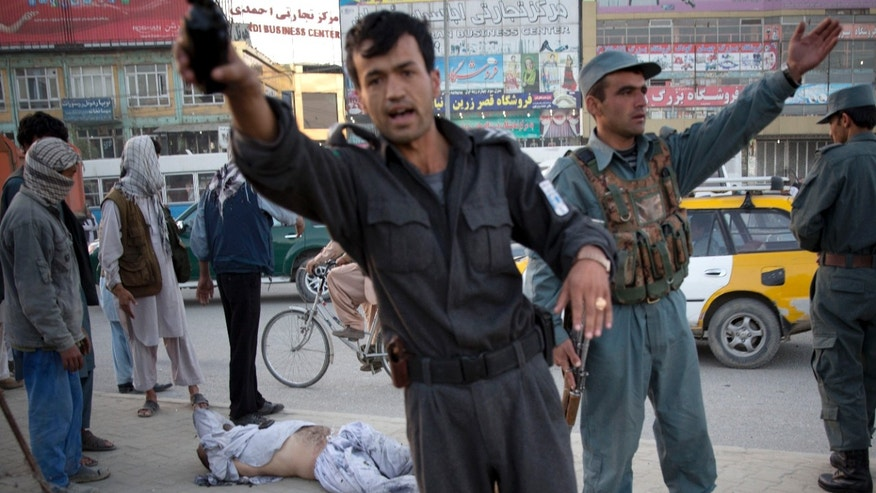 Afghan police men push people away after a bomb exploded under a car, leaving the driver dead, in the center of Kabul, Afghanistan, Monday, Oct. 21, 2013. The Afghan Interior ministry confirmed that it was a magnetic bomb that destroyed the vehicle and killed the driver in the early morning rush hour. (AP Photo/Anja Niedringhaus)
