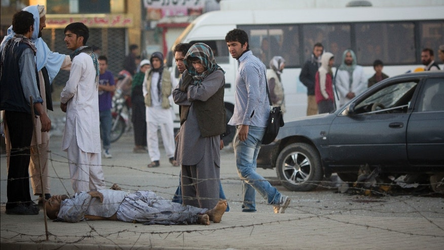 Afghan's surround a dead man after a bomb exploded under a car, on the right, leaving the driver dead, in the center of Kabul, Afghanistan, Monday, Oct. 21, 2013. The Afghan Interior ministry confirmed that it was a magnetic bomb that destroyed the vehicle and killed the driver in the early morning rush hours. (AP Photo/Anja Niedringhaus)