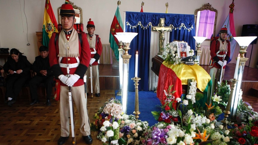 Soldiers stand around the coffin of Bolivian soldier Oscar Gironda during a wake at the military barracks in La Paz, Bolivia,  Sunday, Oct. 20, 2013. A group of locals armed with rifles and knives attacked police and soldiers who were destroying illegal coca crops in the community of Miraflores, near the town of Apolo, 150 km. ( 90 miles ) north of La Paz killing a police officer, an army lieutenant and injuring at least 20 others, authorities said. It is believed to be the first fatal attack on a coca eradication team since Evo Morales, a coca-growers' union leader, was elected president nearly eight years ago. (AP Photo/Juan Karita)
