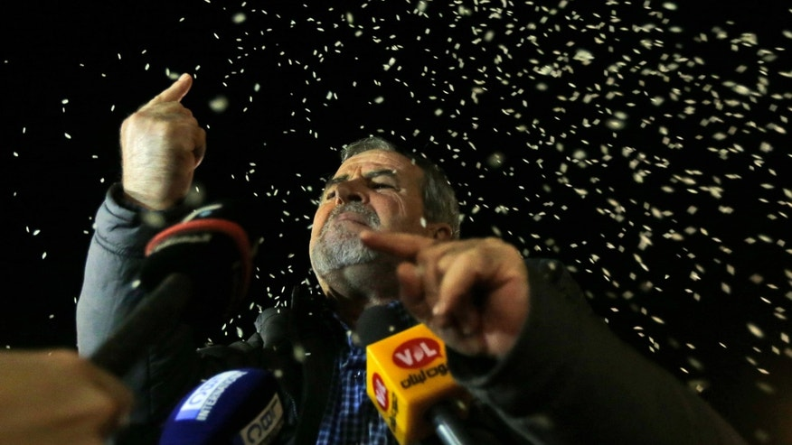 ADDS NAME - Ali Zougheib, one of the nine Lebanese Shiite pilgrims who were kidnapped by a rebel faction in northern Syria in May 2012, reacts as rice is seen throw over him, upon his arrival at Rafik Hariri international airport, in Beirut, Lebanon, Saturday, Oct. 19, 2013. Two Turkish pilots held hostage in Lebanon and nine Lebanese pilgrims abducted in Syria returned home Saturday night, part of an ambitious three-way deal cutting across the Syrian civil war.(AP Photo/Hussein Malla)