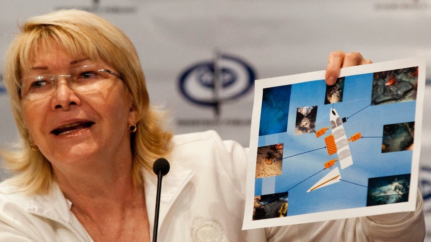 Venezuela's Attorney General Luisa Ortega Diaz holds up an image showing evidence recovered from the small plane YV2615 that crashed in January in the Los Roques islands during a press conference in Caracas, Venezuela, Monday, Oct. 21, 2013. Venezuelan authorities say navy divers also have recovered five bodies from the plane that was carrying six people, including the CEO of the Italian fashion house Missoni. Attorney General Luisa Ortega told reporters on Monday it would take up to a month to positively identify the remains, which she said were recovered between Oct. 12 and 19. On board when it went down were the 58-year-old Vittorio Missoni, his wife, two Italian friends and the two-man Venezuelan crew.(AP Photo/Ariana Cubillos)