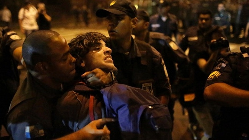 Oct. 15, 2013: A Brazilian police officer detains a demonstrator during clashes with a small group of protesters, after a march of striking teachers took place to mark National Teachers Day in Rio de Janeiro, Brazil. As most demonstrators headed home, hundreds of masked members of the so-called Black Bloc anarchist group started hurling gasoline bombs, rocks, bottles and pieces of wood at police who had accompanied the protest marches. Police used tear gas and percussion grenades to disperse the violent activists.