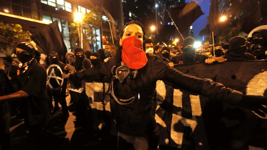 Oct. 15, 2013: In this file photo, masked members of the Black Bloc anarchist group join in a march in support of striking teachers in Rio de Janeiro, Brazil. The Black Bloc, a violent form of protest and vandalism that emerged in the 1980s in West Germany, has become a driving force in Brazil behind protests in recent weeks. The young Brazilians are following the main anti-capitalist tenets of earlier versions, smashing scores of banks and multinational businesses during demonstrations and directly confronting riot police.