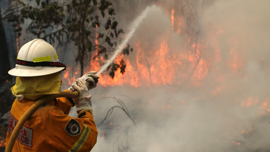 A firefighter tries to control flames near houses at Bilpin, 75 kilometers (47 miles) west of Sydney, Australia, Tuesday, Oct. 22, 2013. Authorities have warned that hotter weather and increased winds are expected and are preparing for the conditions to worsen. (AP Photo/Rob Griffith)