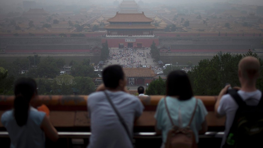 "In this photo taken on June 29, 2013, tourists look at the Forbidden City from the top of Jinshan hill on a hazy day in Beijing, China. China's tourism industry has grown at a fast pace since the country began free market-style economic reforms three decades ago. However, it's latest tourism slogan ""Beautiful China"" has been derided as particularly inept at a time when record-busting smog has drawn attention to the environmental and health costs of China's unfettered industrialization. Some point to unsophisticated marketing as an explanation.  (AP Photo/Alexander F. Yuan)"