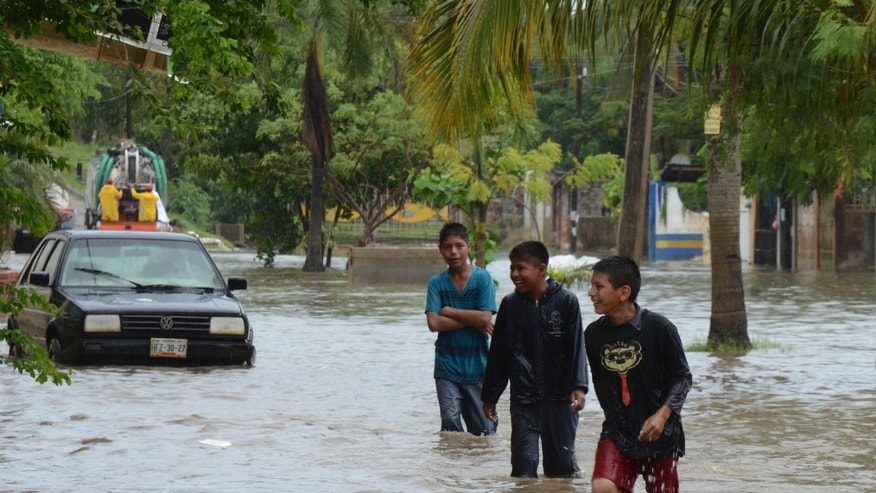 Young men play in a flooded street in Acapulco, Mexico, Monday, Oct. 21, 2013. The area is on alert as Hurricane Raymond gained more strength and threatened to hurl heavy rains onto a sodden region already devastated by last month's Tropical Storm Manuel. (AP Photo/Bernandino Hernandez)