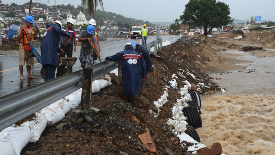 Workers reinforce a road with sandbags in Acapulco, Mexico, Monday Oct. 21, 2013. The area is on alert as Hurricane Raymond gained more strength and threatened to hurl heavy rains onto a sodden region already devastated by last month's Tropical Storm Manuel. (AP Photo/Bernandino Hernandez)