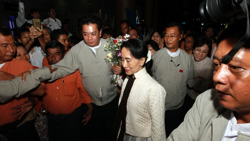 Myanmar opposition leader Aung San Suu Kyi, center, arrives at Yangon International Airport Friday, Oct. 18, 2013, in Yangon, Myanmar. Suu Kyi, leaving for a five-nation tour in Europe, will receive the EU's Sakharov human rights prize in Strasbourg, France in November along with Pakistani schoolgirl and girls' education campaigner Malala Yousafzai who survived a Taliban assassination and South Africa's Nelson Mandela. (AP Photo/Khin Maung Win)