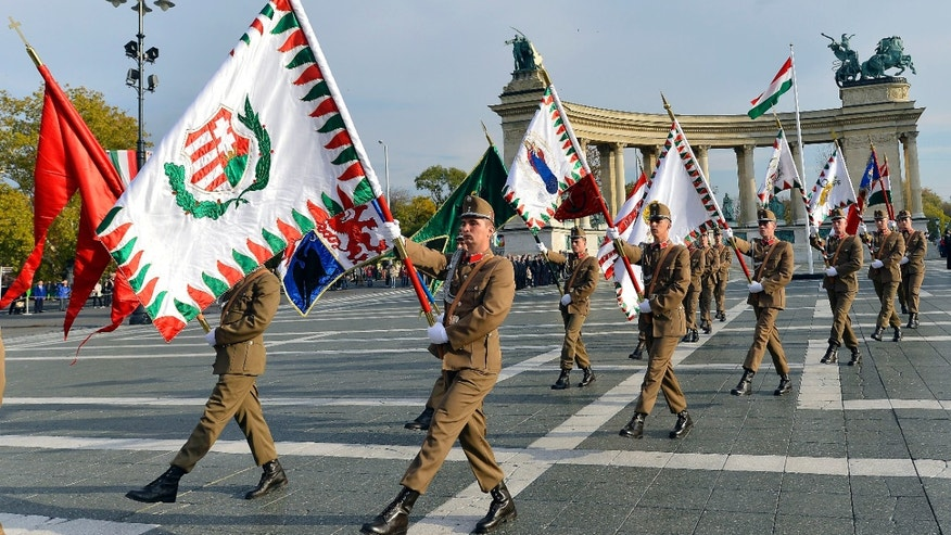 Honour guards hold historic flags as they march during a ceremony to mark the 57th anniversary of the Hungarian revolution and war of independence against communist rule and the Soviet Union in 1956 on the Heroes' Square in Budapest, Hungary, Wednesday, Oct. 23, 2013.  (AP Photo/MTI,Tibor Illyes)