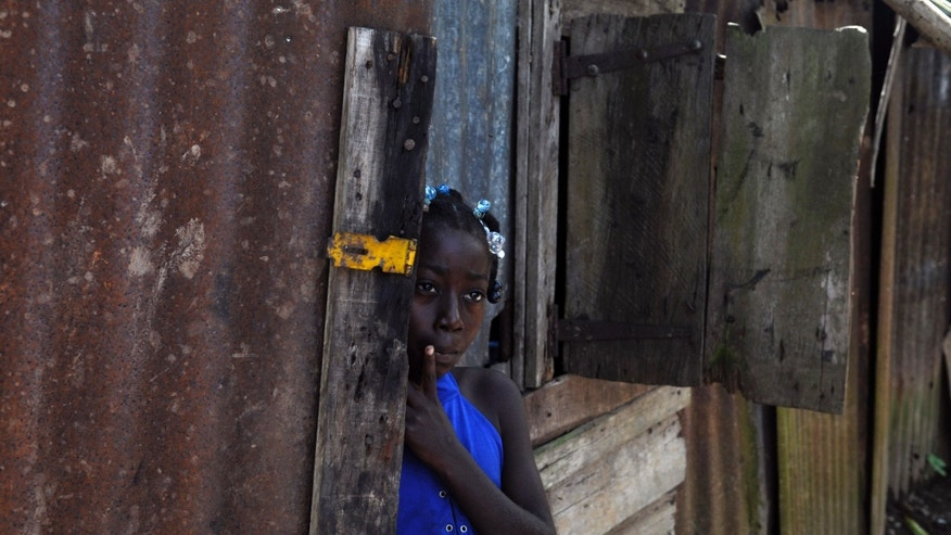 In this Sept. 30, 2013 photo, Maria Julia Deguis, 10, looks out from her home in Los Jovillos village, known as a batey, in the Monte Plata province of the Dominican Republic. Maria, like with her mother and brother, is of Haitian descent and was born in the D.R., but she may lose her citizenship, and the rights that go along with it, because of a recent Constitutional Court decision. (AP Photo/Manuel Diaz)