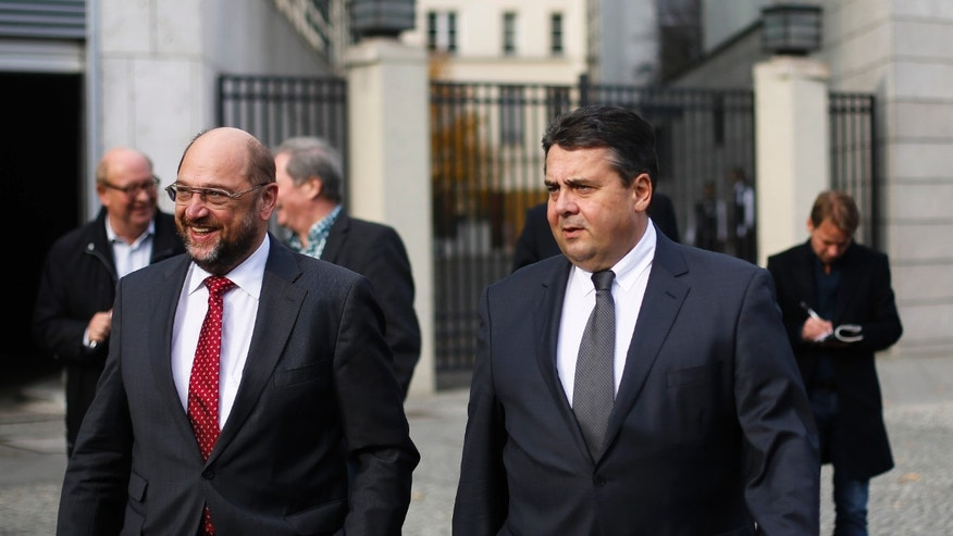 German Social Democratic Party chairman Sigmar Gabriel, center, and the President of the European Parliament Social Democrat Martin Schulz, left, arrive for coalition talks at the Christian Union party headquarters in Berlin, Wednesday, Oct. 23, 2013. Following the Sept. 22 national elections Chancellor Angela Merkel and her Christian parties' block start coalition talks on forming a new government with the Social Democratic Party. (AP Photo/Markus Schreiber)