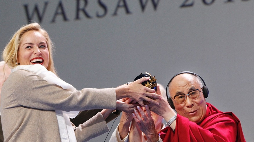 US actress Sharon Stone,left, receives the Nobel Peace laureates summit Peace Prize from Dalai Lama in Warsaw, Poland, Wednesday, Oct. 23, 2013. Stone was awarded in recognition of her activities against HIV and AIDS. (AP Photo/Czarek Sokolowski)