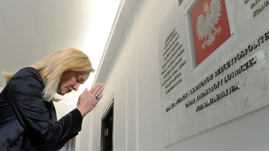 US actress Sharon Stone bows in front of a plaque dedicated to the lawmakers killed in the 2010 presidential plane crash as she visits the Polish parliament  in Warsaw, Poland,  Tuesday, Oct. 22, 2013. Stone came to Warsaw to attend the Nobel Peace Prize laureates meeting and to receive the Peace Summit Award in recognition of her activities against HIV and AIDS. Nobel Peace Prize laureates are discussing challenges facing the world: armed conflicts, economic inequality and migration. The 13th annual summit that opened Monday is held for the first time in Eastern Europe to mark 30 years since former Polish President Lech Walesa was awarded the prize for leading Solidarity movement that toppled communism in Poland. (AP Photo/Alik Keplicz)
