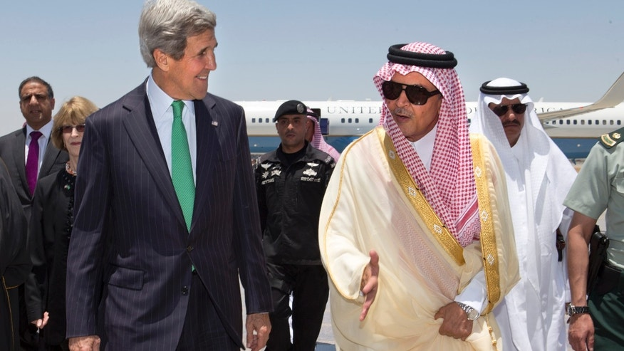 FILE - In this Tuesday, June 25, 2013 file photo, U.S. Secretary of State John Kerry, left, is greeted by Saudi Foreign Minister Prince Saud al-Faisal upon arrival in Jeddah, Saudi Arabia. One day, Saudi Arabia looks to spend $6.8 billion in its latest buying spree of American weapons. Two days later, the kingdom vents its anger at the U.S. 's Mideast policy by snubbing a seat on the U.N. Security Council in a show of discontent. A mix of both customer and critic, Saudi Arabia is trying to carve out its own path to counter U.S. moves such as outreach to Iran, while knowing it still needs its longtime ally as a powerful big brother. (AP Photo/Jacquelyn Martin, Pool, File)