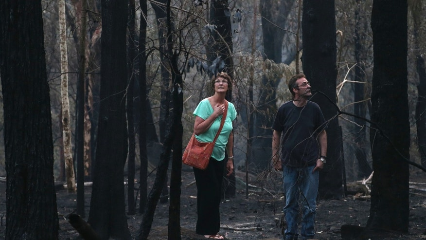 Jennifer Schweinsberg and her son David walk around the back yard of their destroyed family home in Sunny Ridge Drive in Winmalee 65 kilometers (40 miles) from Sydney in  Australia, Tuesday, Oct. 22, 2013 after a wildfire swept through the street burning it and several other homes on Oct 18, 2013. Wildfires have destroyed more than 200 properties including 122 homes with authorities asking residents and people to prepare for worsened conditions Wednesday.(AP Photo/Rob Griffith)