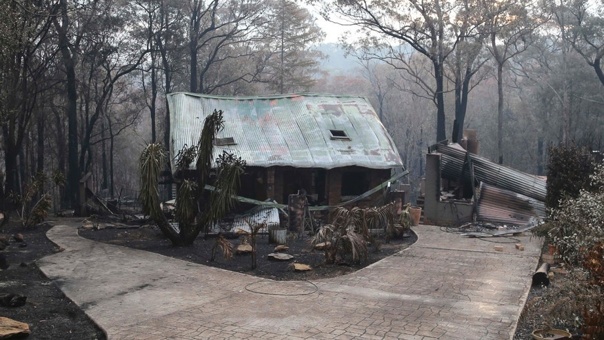 A house sits in ruins in Sunny Ridge Drive in Winmalee 65 kilometers (40 miles) from Sydney in  Australia,  Tuesday, Oct. 22, 2013 after a wildfire swept through the street burning several homes on Oct 18, 2013. Wildfires have destroyed more than 200 properties including 122 homes with authorities asking residents and people to prepare for worsened conditions Wednesday.(AP Photo/Rob Griffith)