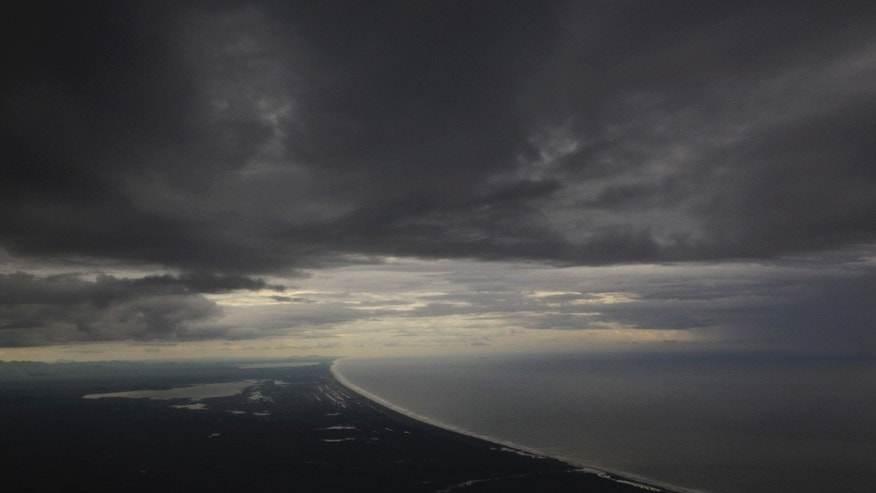 An aerial view seen from an airplane window, south of Acapulco, Punta Diamante, Mexico, Tuesday, Oct. 22, 2013. Hurricane Raymond weakened to barely a Category 1 storm Tuesday while still stalled off Mexico's Pacific coast, pumping rain onto an already sodden region recovering from a battering by a tropical storm last month.  (AP Photo/Marco Ugarte)