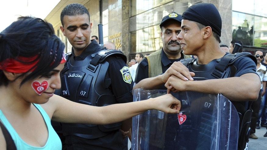 A woman puts a heart shaped sticker on a police officer's shield during a protest in Tunis, Wednesday, Oct. 23, 2013, calling for the resignation of the government.  Some thousands demonstrated in Tunisia on the day of the opening of the country's national dialogue calling for the Islamist-led government to keep its promise and resign to allow fresh elections. (AP Photo/Hassene Dridi)