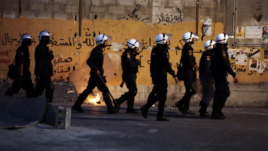 "Riot police look for Bahraini anti-government protesters during clashes after the funeral for a 17-year-old boy in Bani Jamra, Bahrain, on Wednesday, Oct. 23, 2013. Authorities said Ali al-Sabagh was killed when an explosive device he was carrying detonated prematurely as he attempted to stage an attack in the tense Gulf nation. Graffiti on the wall includes, ""steadfast, resistance, unity"" and a religious verse about fighting injustice. (AP Photo/Hasan Jamali)"