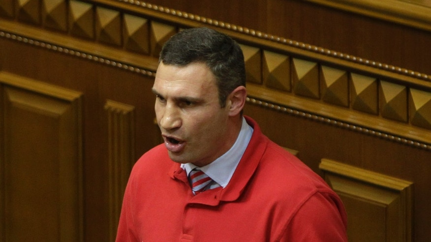 Chairman of the Ukrainian opposition party Udar (Punch) and WBC Heavyweight Champion boxer Vitali Klitschko, speaks to lawmakers in Kiev, Ukraine, Thursday, Oct. 24, 2013.  Klichko announced Thursday that he would run for President in 2015. The words emblazoned on the shirt read, 'Ukraine is Europe'.(AP Photo/Sergei Chuzavkov)