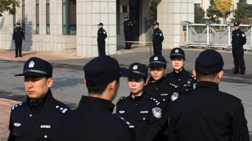 Police officers change shifts outside Shandong Provincial Higher People's Court in Jinan where ruling to ousted Chinese politician Bo Xilai's appeal against his conviction will be handed down, in eastern China's Shandong province, Friday, Oct. 25, 2013. (AP Photo/Alexander F. Yuan)