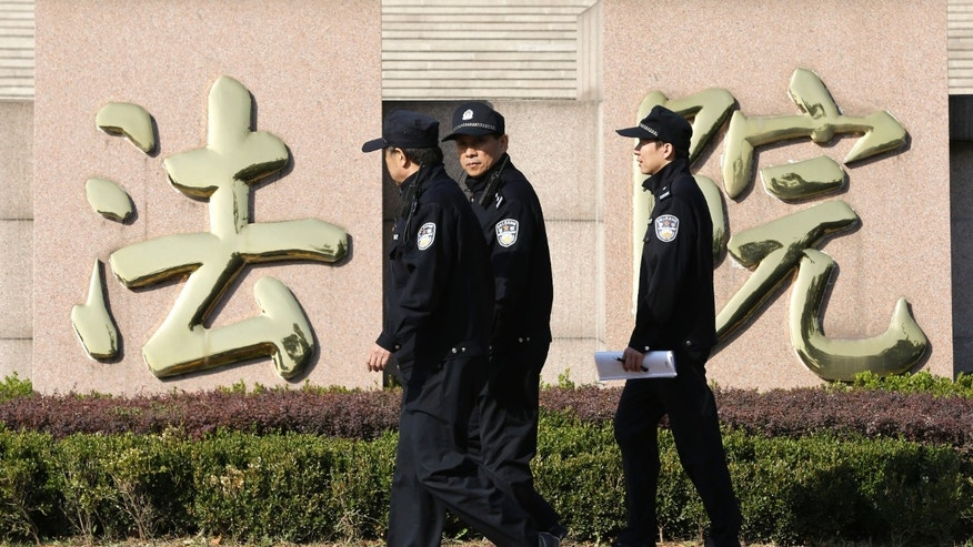 "Policemen walk past Chinese characters reading ""courthouse,"" which is part of the sign for Shandong Province Supreme People's Court in Jinan, in eastern China's Shandong province, Thursday, Oct. 24, 2013. The court will hold a hearing on Friday to rule on disgraced politician Bo Xilai's appeal against the guilty verdict and life imprisonment he was handed last month. Bo was found guilty of embezzlement, bribery and abuse of power by a lower court last month and sentenced to life in prison. He has denied the charges. (AP Photo/Alexander F. Yuan)"