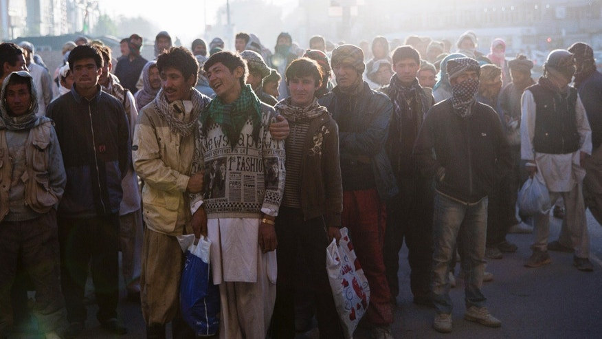 In this Saturday, Oct. 19, 2013 photo, Afghan day laborers gather before dawn hoping to be picked for work at an intersection in Kabul, Afghanistan. The jobs are often backbreaking, always temporary and most likely will earn them a few dollars for a day's work. (AP Photo/Anja Niedringhaus)
