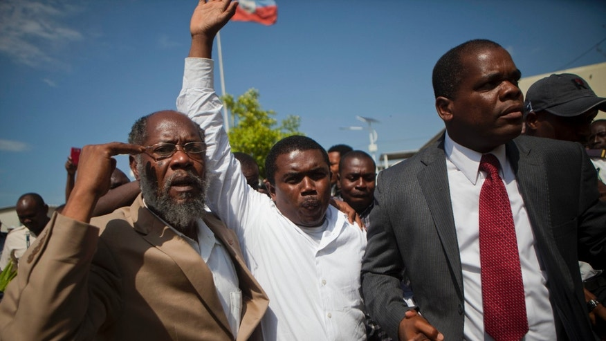 Attorney Andre Michel is flanked by two Haitian senators as he is taken away from the courthouse to a waiting vehicle, in Port-au-Prince Haiti, Wednesday, Oct. 23, 2013. Supporters of Michel who has brought corruption cases against Haiti's government whisked him away from a courthouse Wednesday as he awaited a hearing after being detained by police. (AP Photo/Dieu Nalio Chery)