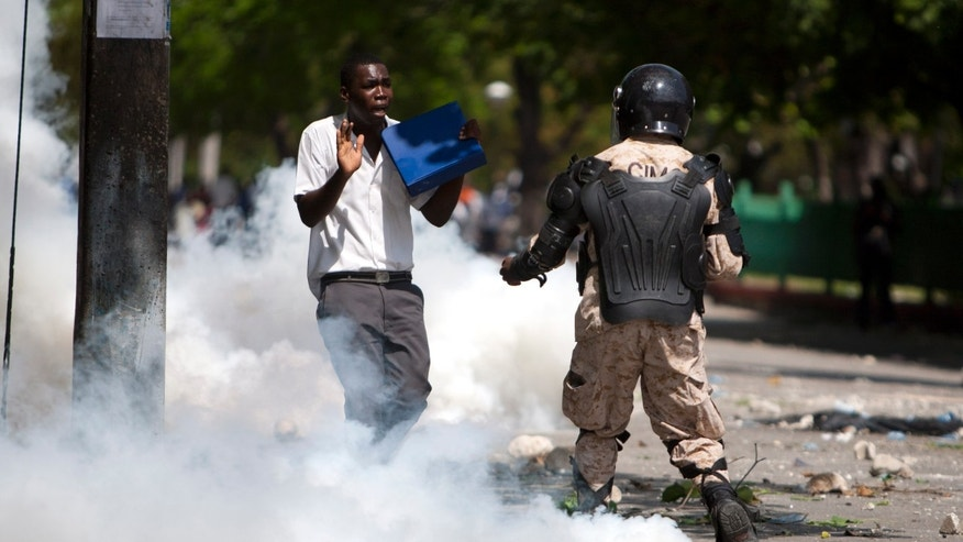 Engulfed in a cloud of tear gas, a student is briefly detained by police during a protest in Port-au-Prince, Haiti, Wednesday, Oct. 23, 2013. Supporters of an opposition figure who has brought corruption cases against Haiti's government protested against his arrest while others whisked him away from the courthouse as a judge prepared to serve an order that he be transferred to the state penitentiary. Prosecutors did not say publicly why Michel was arrested. (AP Photo/Dieu Nalio Chery)