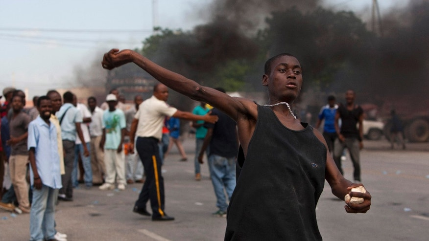 A supporter of an opposition figure who has brought corruption cases against Haiti's government throws rocks at police during a protest outside a courthouse in Port-au-Prince, Haiti, Wednesday, Oct. 23, 2013. Supporters of attorney Andre Michel, who has brought corruption cases against Haiti's government, protested against his arrest while others whisked him away from the courthouse as a judge prepared to serve an order that he be transferred to the state penitentiary. Prosecutors did not say publicly why Michel was arrested. (AP Photo/Dieu Nalio Chery)