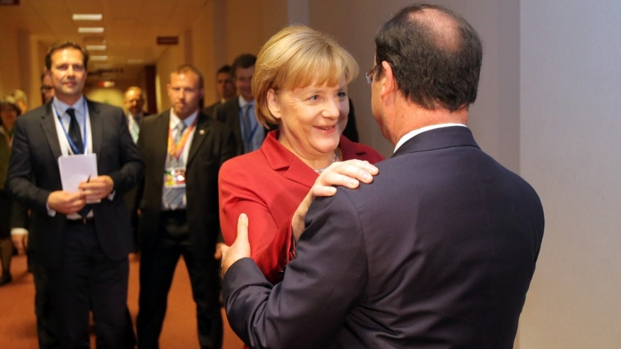German Chancellor Angela Merkel, second right, speaks with French President Francois Hollande, right, prior to a bilateral meeting on the sidelines of an EU summit on Thursday, Oct. 24, 2013. A two-day summit meeting of EU leaders is likely to be diverted from its official agenda, economic recovery and migration, after German Chancellor Angela Merkel complained to U.S. President Barack Obama that U.S. intelligence may have monitored her mobile phone. (AP Photo/Michel Euler, Pool)