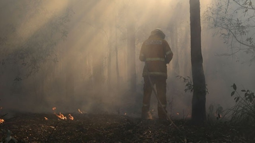 October 23, 2013: A firefighter mops up after a firestorm swept through a property in Bilpin, 47 miles from Sydney, Australia (AP Photo)