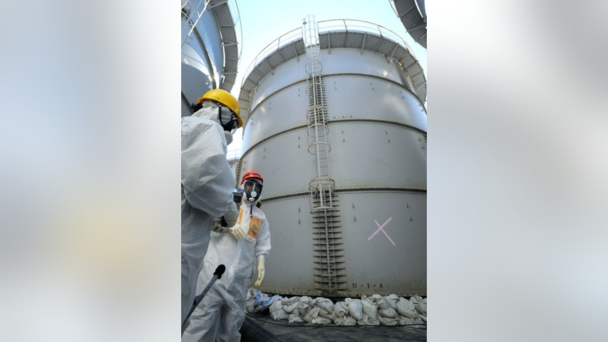"FILE - In this Aug. 26, 2013 file photo, Japanese Trade Minister Toshimitsu Motegi, second from left, in a protective gear inspects storage tanks, including the one caused contaminated water leak, marked with ""X,"" at the Fukushima Dai-ichi nuclear plant at Okuma town in Fukushima prefecture, northeastern Japan. A string of mishaps this year at Japan's crippled Fukushima nuclear power plant, which was swamped by a tsunami in 2011, is raising doubts about the operator's ability to tackle the crisis and prompting concern that another disaster could be in the making. (AP Photo/Kyodo News, File) JAPAN OUT, MANDATORY CREDIT"