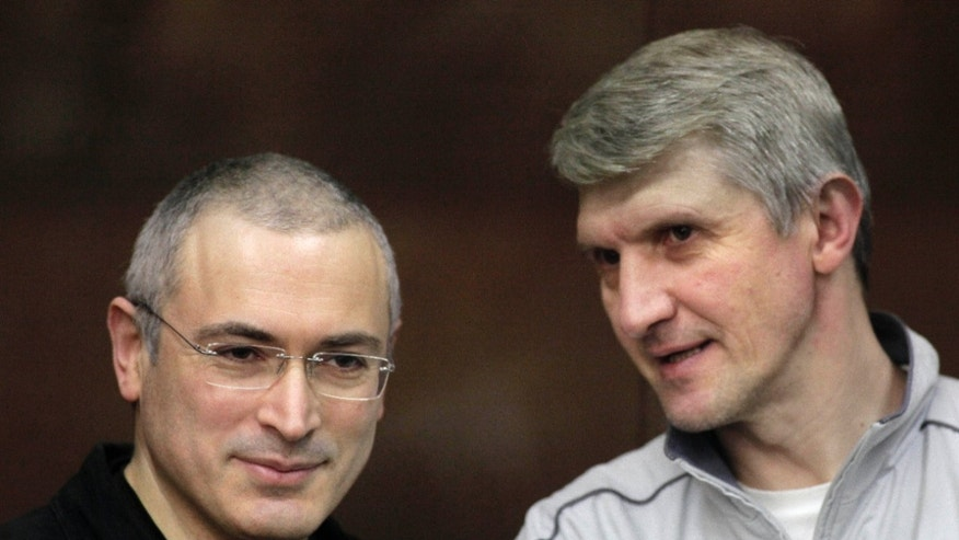 FILE - In this file photo taken on Thursday Dec. 30, 2010, former oil tycoon Mikhail Khodorkovsky, left, and his co-defendant Platon Lebedev talk behind a glass enclosure at a court room in Moscow, Russia. Khodorkovsky marks 10 years since his arrest, which has become a key turning point in Russia's recent history. His arrest _ widely seen as a punishment for challenging President Vladimir Putin's power _ and the subsequent dismantling of his Yukos oil company sent a chilling signal to others and allowed Putin to consolidate his power. (AP Photo/Alexander Zemlianichenko Jr, File)