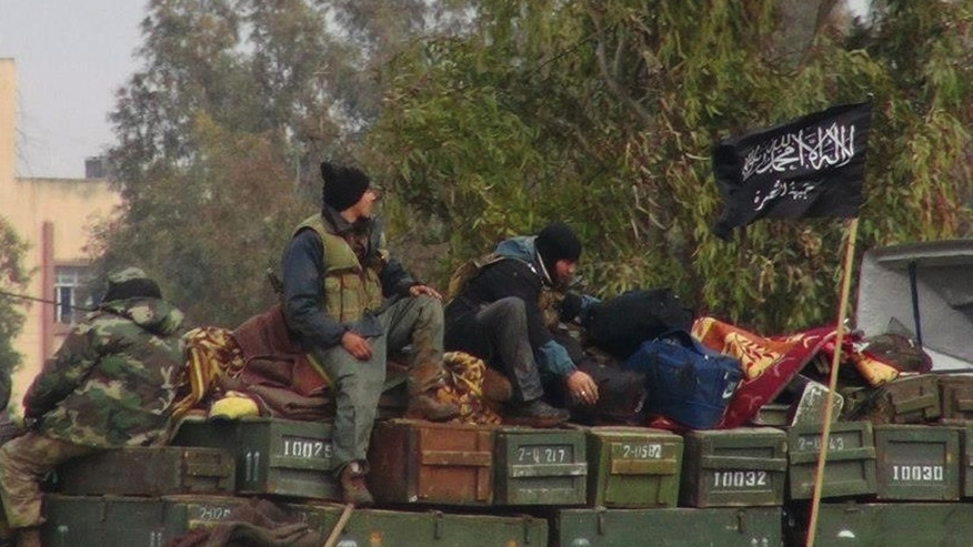 FILE - In this Friday, Jan. 11, 2013 file citizen journalism image provided by Edlib News Network, ENN, which has been authenticated based on its contents and other AP reporting, shows rebels from al-Qaida affiliated Jabhat al-Nusra, as they sit on a truck full of ammunition, at Taftanaz air base,  that was captured by the rebels, in Idlib province, northern Syria. An Islamist extremist group affiliated with al-Qaida, Jabhat al-Nusra has emerged as one of the most powerful rebel factions on the battlefield.(AP Photo/Edlib News Network, ENN, File)