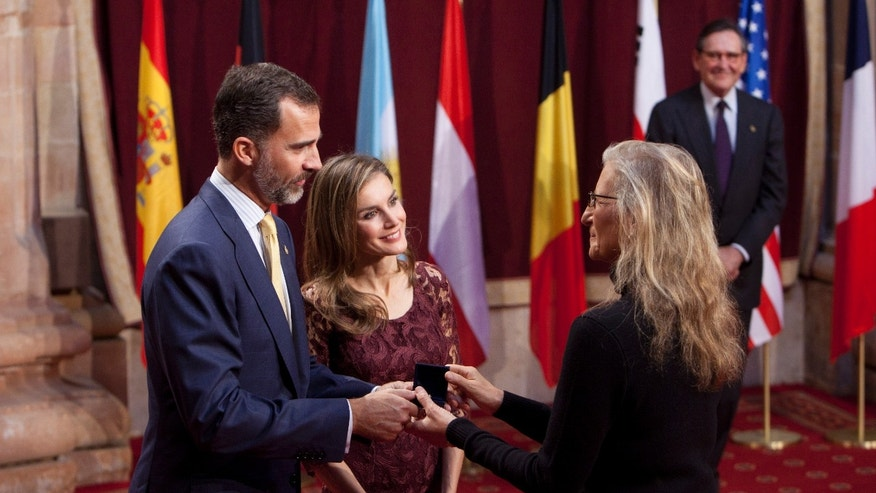 Spain's Crown Prince Felipe, left, and Princess Letizia Ortiz, center, give an emblem to U.S. photographer Annie Leibovitz, right, in Oviedo, northern Spain, Friday Oct. 25, 2013. Annie Leibovitz will receive the 2013 Prince of Asturias Award for Communication and Humanities during a ceremony Friday evening. (AP Photo/Abraham Caro Marin)