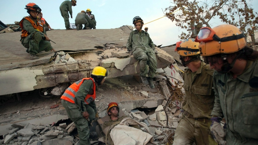 "FILE - In this Sunday, Oct. 21, 2012 file photo, Israeli soldiers from the Home Front Command attend to a soldier acting as a survivor in the rubble of a school during a drill simulating an earthquake in Holon, Israel. As if Israel doesn't have enough to worry about, a problem millions of years in the making is now literally sending shockwaves throughout the country. Five mid-size earthquakes measuring between magnitude 3 and 4 have hit the Sea of Galilee area this past week, raising fears that the ""big one"" is on its way and could carry with it devastation that would dwarf what the country has faced from wars, violent Palestinian uprisings and even a potential nuclear attack from Iran.(AP Photo/Ariel Schalit, File)"